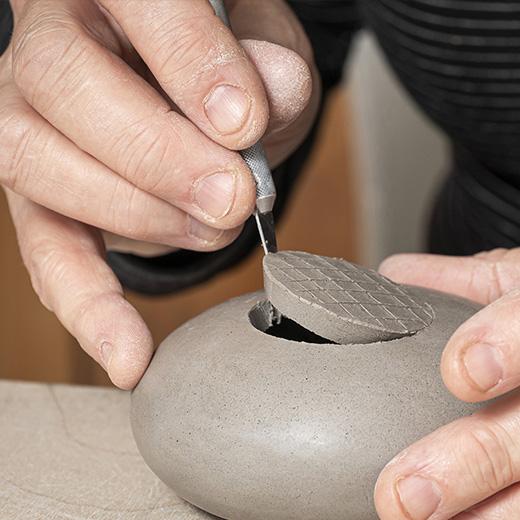 Hilde Evenepoel présentant une urne faite à la main